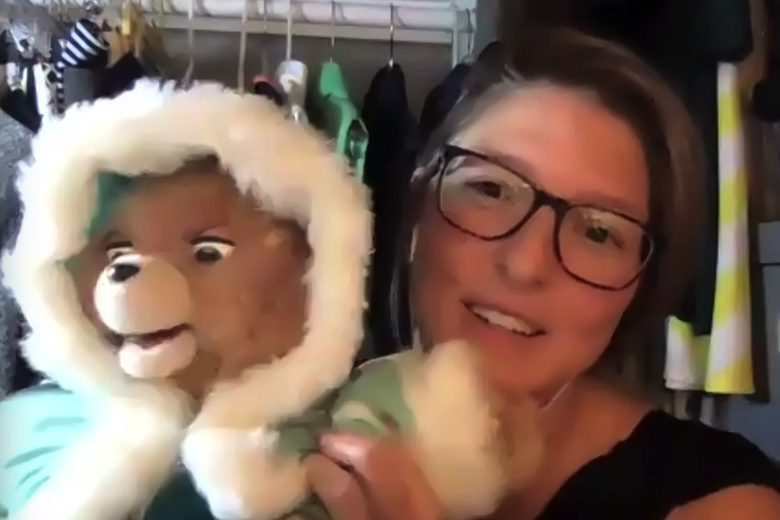 Elizabeth Newcamp holds up a Teddy Ruxpin toy that is wearing a blue coat.