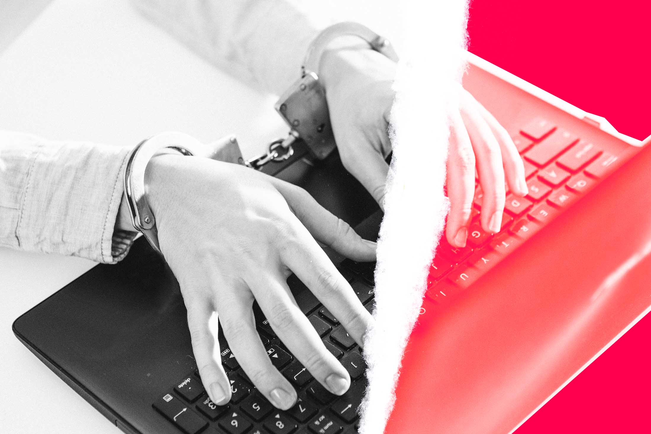 Photo illustration of handcuffed hands typing on a laptop, with a tear running through the center of the image.