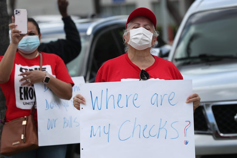 "A protester in a face mask holds a sign that says, ""Where are my checks?"""