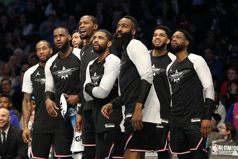 Members of Team LeBron watch play from the bench during the 2019 NBA All-Star Game.