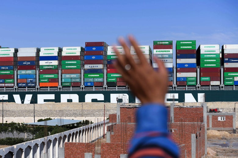 "A man waves at the Panama-flagged MV ""Ever Given"" container ship as it is tugged in Egypt's Suez Canal after it was fully dislodged from the banks, near Suez city, on March 29, 2021."
