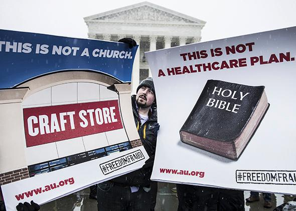 Activists hold signs outside the Supreme Court on March 25, 2014, as the court hears arguments in Sebelius v. Hobby Lobby.