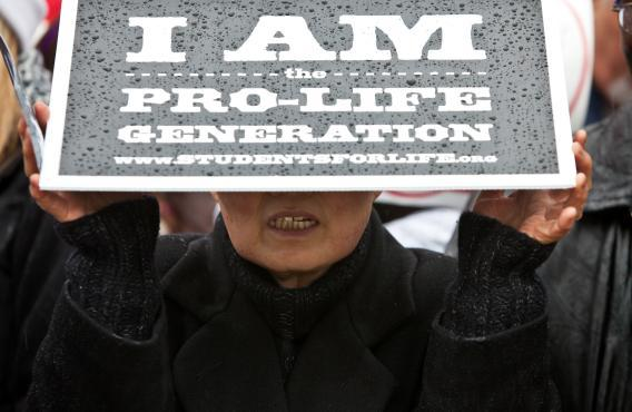 A woman shields herself from the rain at the March for Life rally in January 2012 in Washington, DC.