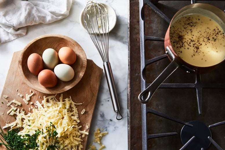 A bowl of five eggs and a mound of grated cheese and minced chives. Nearby, a pan filled with yellow sauce, on a stovetop.