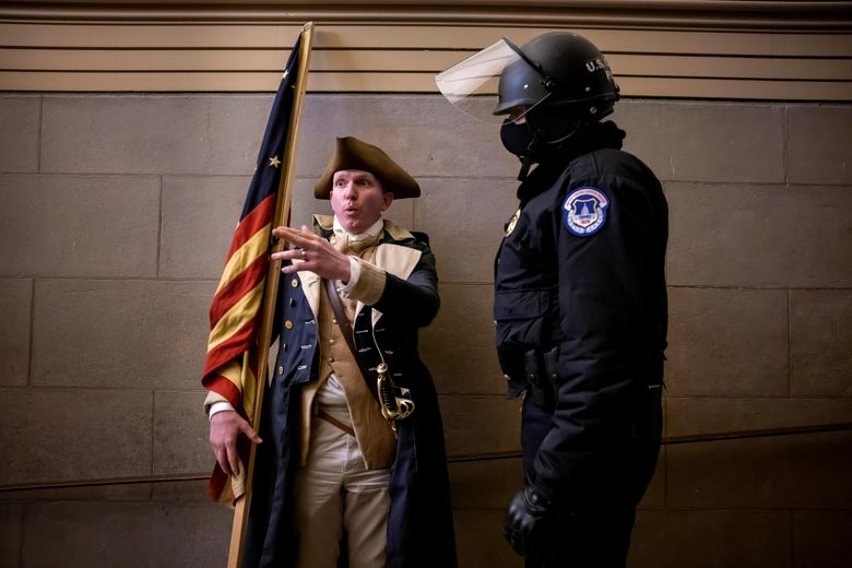 A man wearing a tricorn hat and colonial-era clothing and holding an old American flag debates with a Capitol Police officer inside the Capitol
