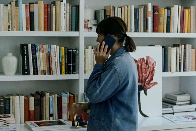 Rashida Jones on the phone, standing in front of her bookshelves.