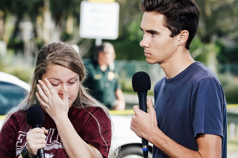 Kelsey Friend and David Hogg, holding microphones.