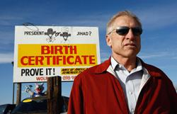 Phil Wolf, owner of Wolf Automotive used car dealership, stands in front of a billboard on his auto lot on November 21, 2009 in Wheat Ridge, Colorado. Click image to expand.
