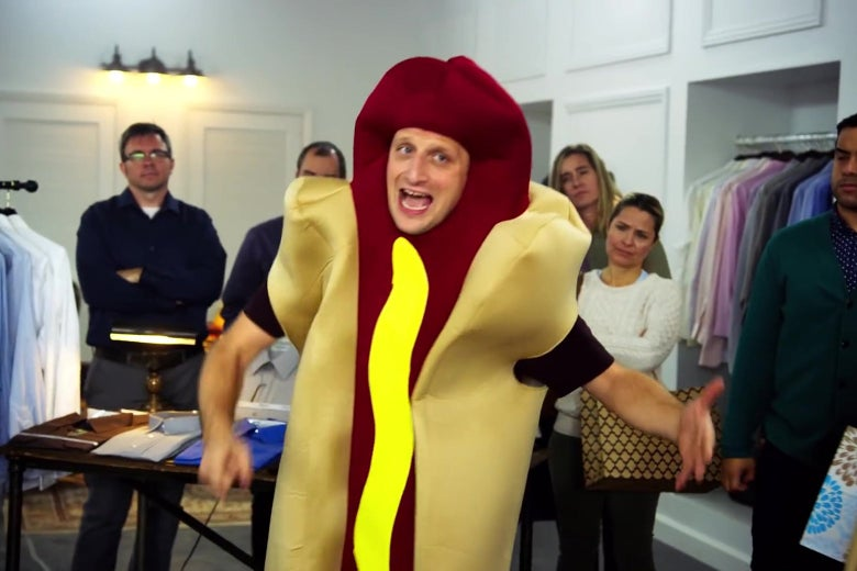 A man in a hot-dog costume stands amid a group of accusing people.
