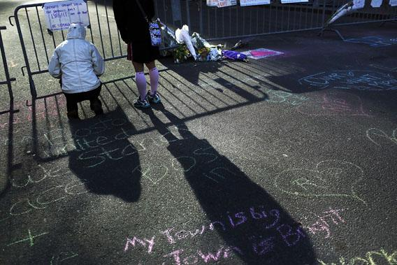 Two women stand  at a street memorial near the scene of twin bombings at the Boston Marathon on April 17, 2013 in Boston, Mass.