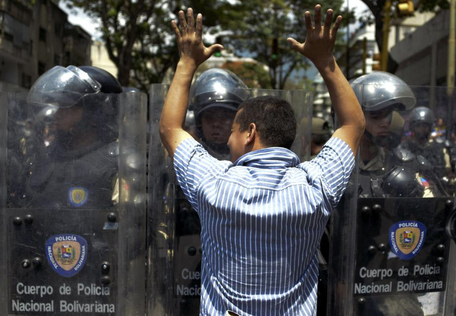A supporter of Leopoldo Lopez, an ardent opponent of Venezuela's socialist government facing an arrest warrant after President Nicolas Maduro ordered his arrest on charges of homicide and inciting violence, faces riot police during a march, on February 18, 2014, in Caracas.