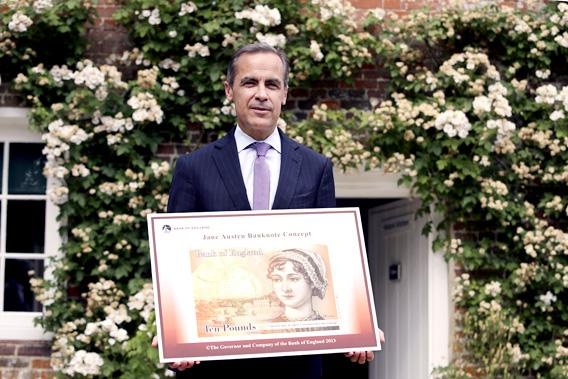 The Governor of the Bank of England, Mark Carney, poses for a photograph with the concept design for the new Bank of England ten pound banknote, featuring author Jane Austen, outside the Jane Austen House Museum in Chawton, southern England July 24, 2013.