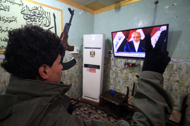 Members of the Hashed al-Shaabi (Popular Mobilisation units) watch the televised statement of Iraqi Prime Minister Haider al-Abadi in the southern city of Basra on December9, 2017.         Abadi declared victory in a three-year war by Iraqi forces to expel the Islamic State jihadist group that at its height endangered Iraq's very existence. / AFP PHOTO / HAIDAR MOHAMMED ALI        (Photo credit should read HAIDAR MOHAMMED ALI/AFP/Getty Images)