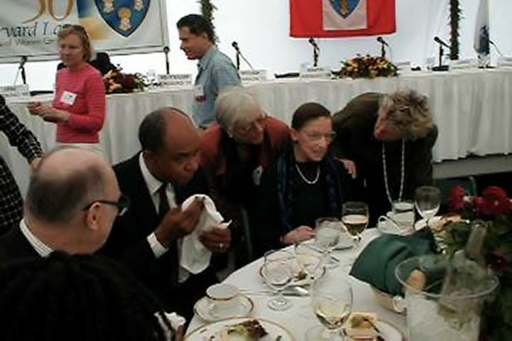 RBG at a table at an event with two women standing on either side of her to speak with her.