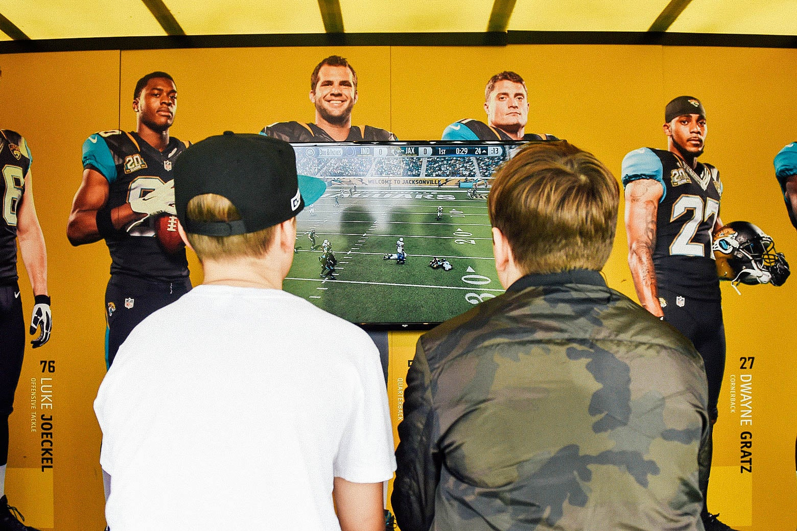 Two young men's backs are toward the gamer as they play Madden on a TV screen.
