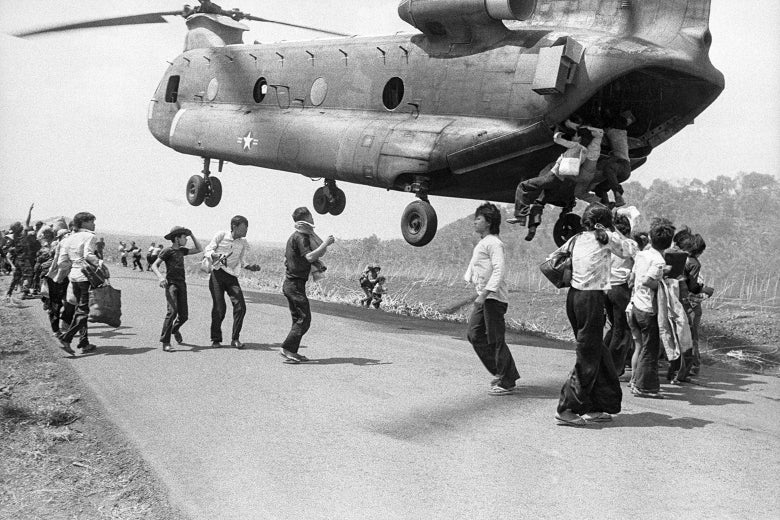 Vietnamese refugees stand on a runway as a U.S. helicopter hovers overhead with three people hanging from the back