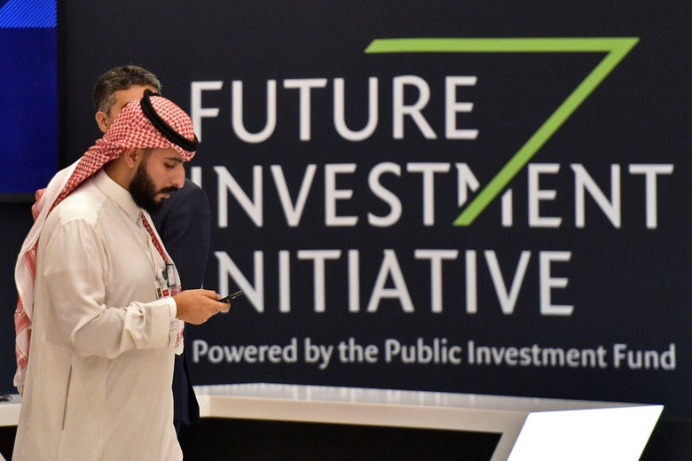 A man in front of the sign for the Future Investment Initiative in Riyadh.