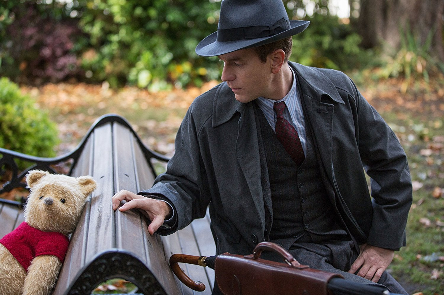 A CGI Winnie the Pooh sits on a live-action park bench, back to back with Christopher Robin (Ewan McGregor).