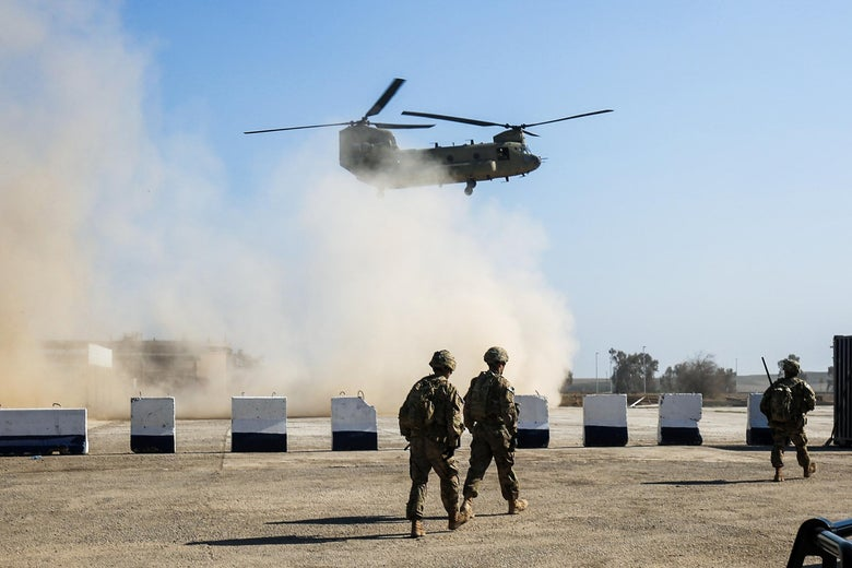 A helicopter takes off above some U.S. soldiers in Iraq.