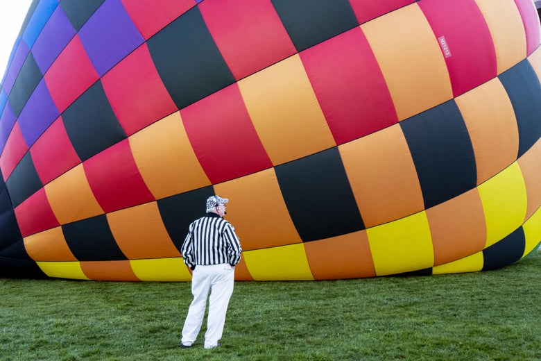 A launch coordinator wearing a black and white striped referee shirt watches a hot air balloon inflate on its side on the grass during the 2018 Albuquerque International Balloon Fiesta