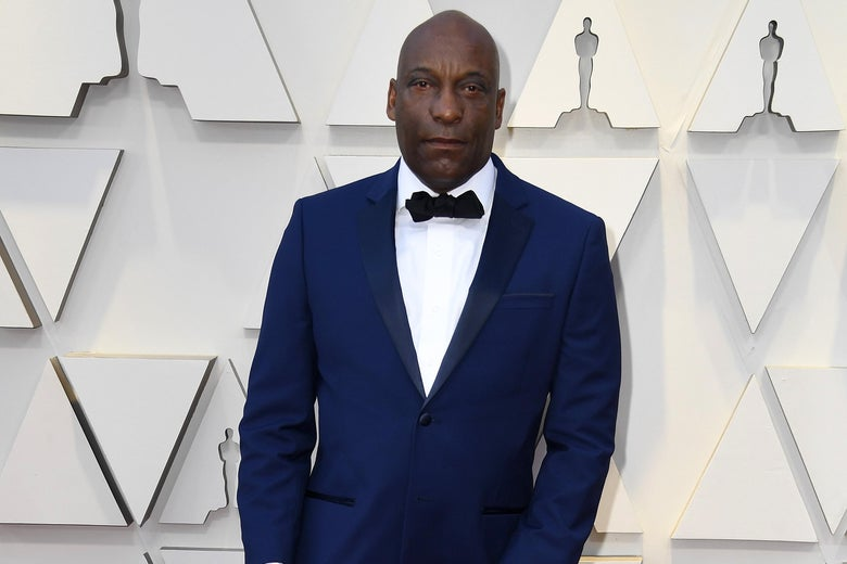John Singleton, in a blue tuxedo with black lapels, on a red carpet.