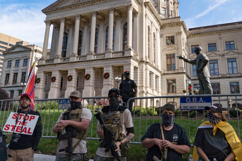Armed men with bandannas over their faces stand in front of the Georgia State Capitol building.