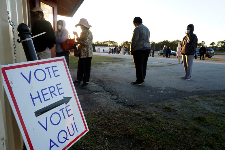 """A """"Vote Here"""" sign in front of a socially distanced line of people outside"""