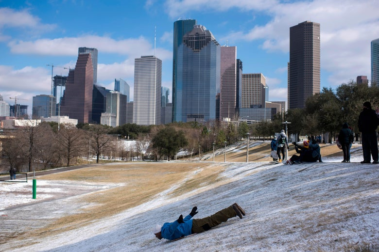 man sliding down a hill with a dusting of snow
