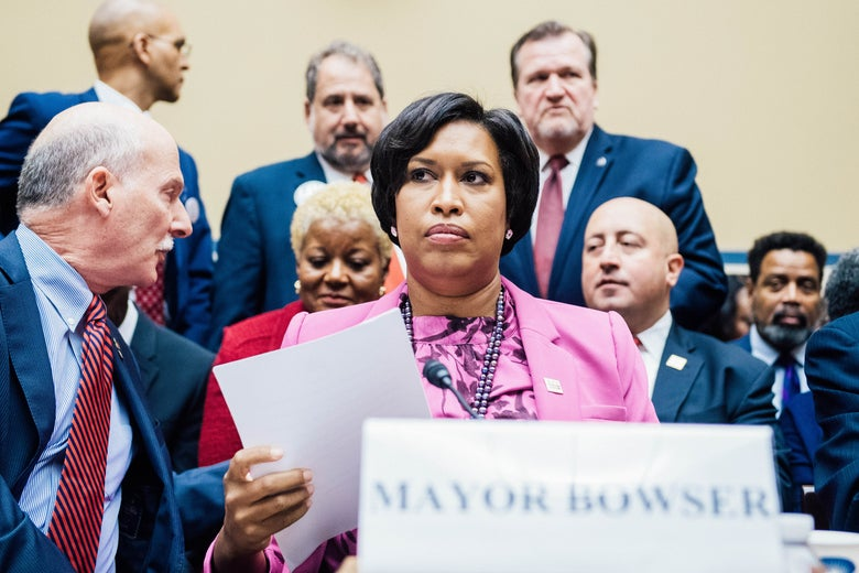"Mendelson turns backward in his seat toward other people at the hearing. Next to him, Bowser holds a piece of paper and sits behind a placard that reads ""MAYOR BOWSER."""