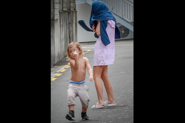 A shirtless young boy flips off the camera. Beside him, a female relative covers her face with pants.