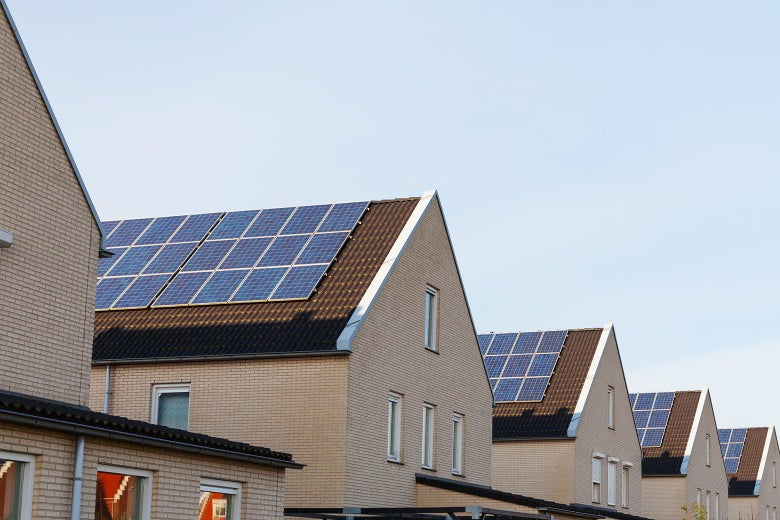 A row of identical houses with solar panels on their roofs.