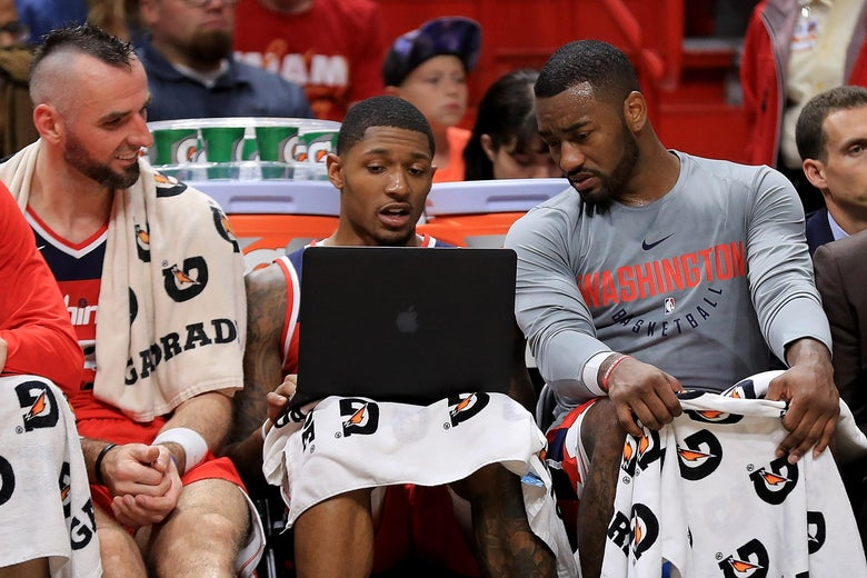 MIAMI, FL - OCTOBER 11: Marcin Gortat #13, Bradley Beal #3, and John Wall #2 of the Washington Wizards look at a laptop during a preseason game against the Miami Heat at American Airlines Arena on October 11, 2017 in Miami, Florida. NOTE TO USER: User expressly acknowledges and agrees that, by downloading and or using this photograph, User is consenting to the terms and conditions of the Getty Images License Agreement.  (Photo by Mike Ehrmann/Getty Images)
