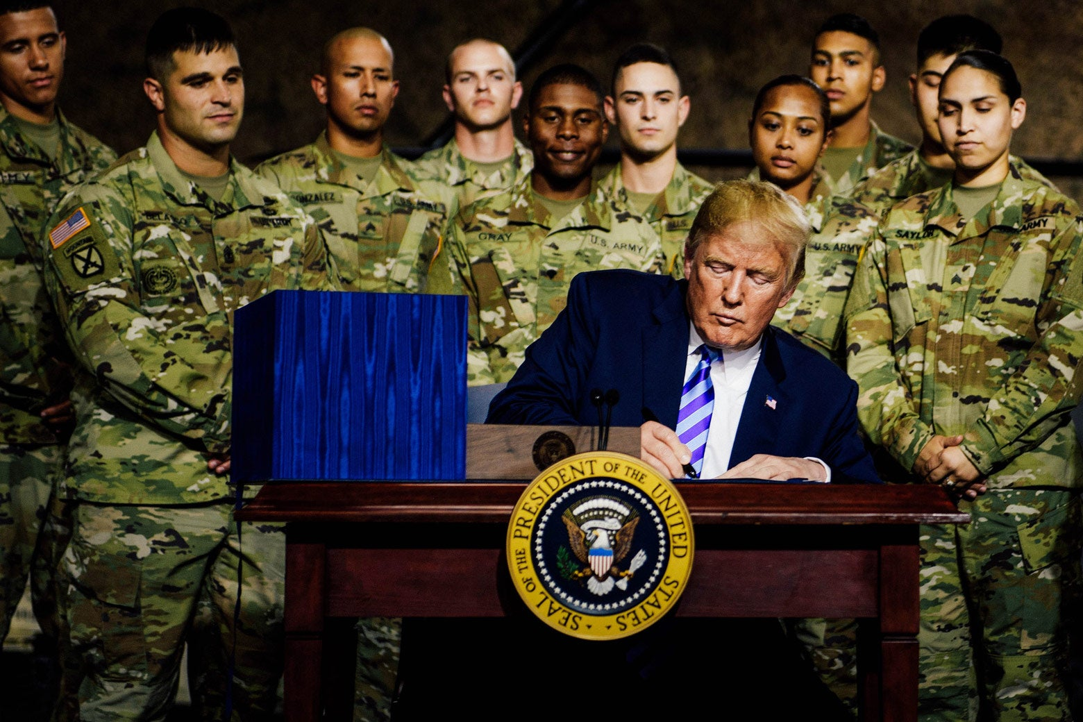 Donald Trump signs something at a desk with service members standing behind him.