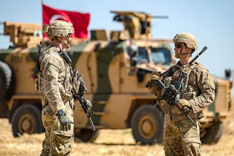 U.S. soldiers chat next to a Turkish military vehicle.