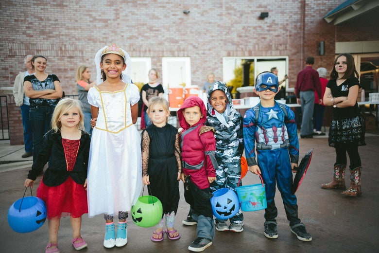 A line of kids in various Halloween costumes.
