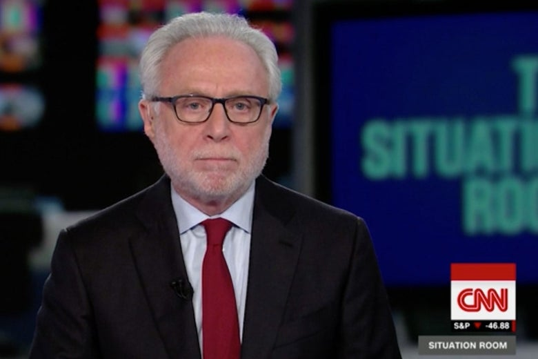 Wolf Blitzer stares at the camera with a blank expression during an episode of The Situation Room on CNN.