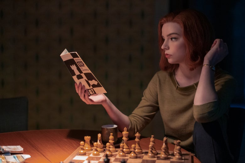 Beth Harmon reads from a book on chess while seated at a table in front of a chessboard.