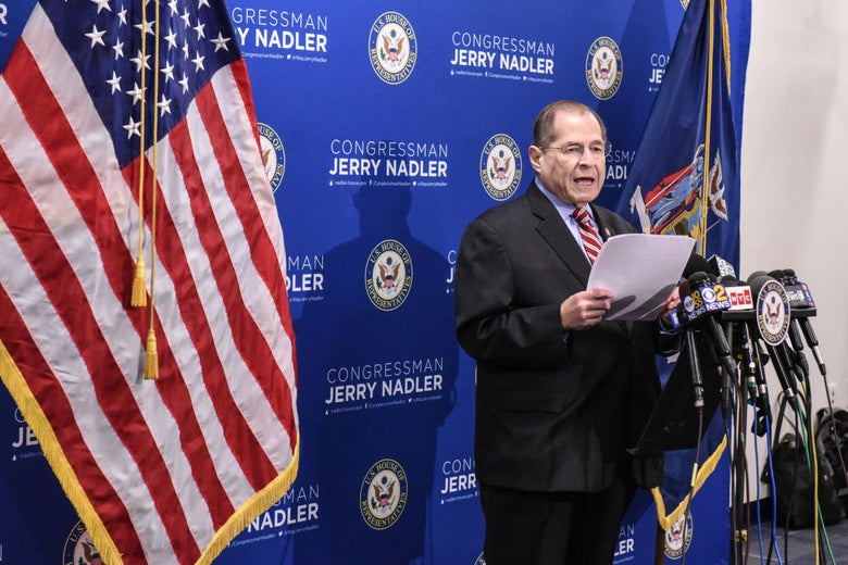 Nadler speaks into a pack of microphones while standing in front of a blue backdrop.