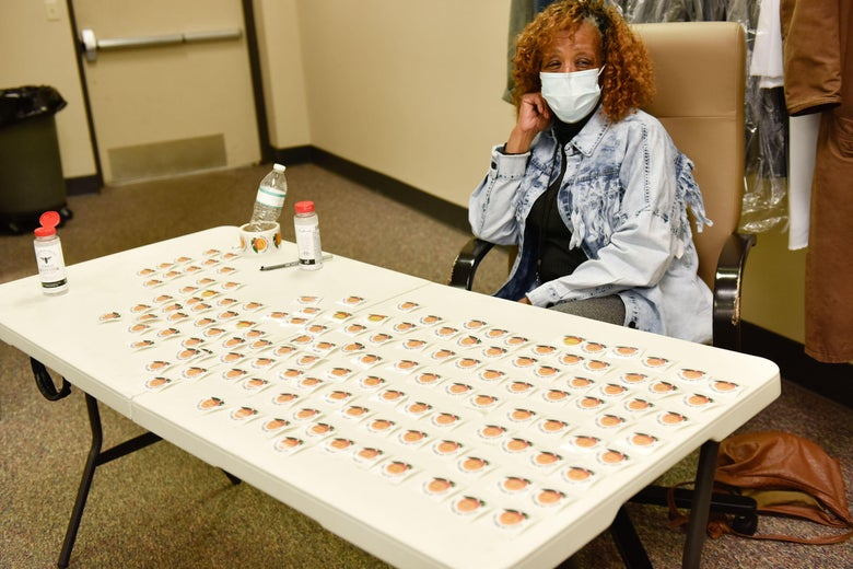 "A woman sits behind a table full of ""I Voted"" stickers"