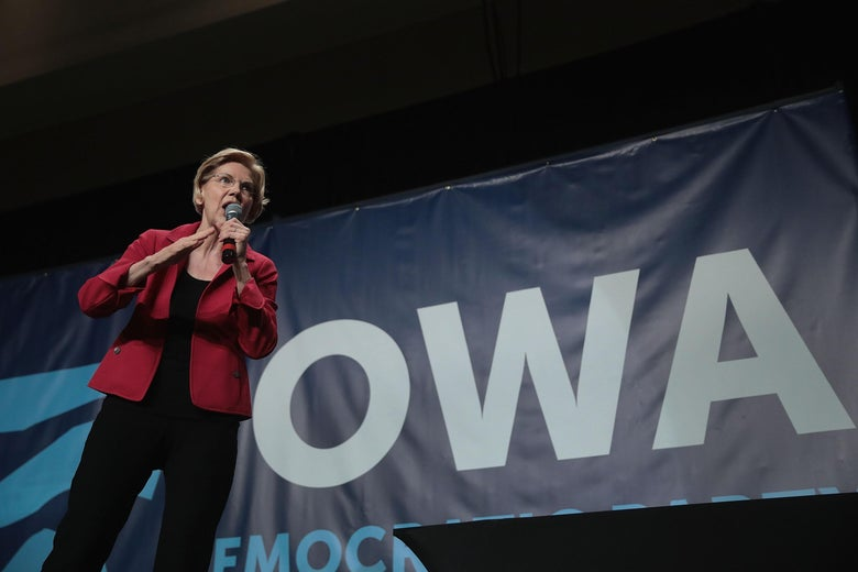 Elizabeth Warren holding and speaking into a mic onstage, campaigning in Cedar Rapids, Iowa.