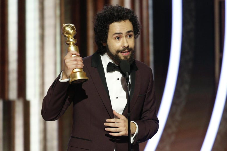 Ramy Youssef onstage, holding up his Golden Globe.