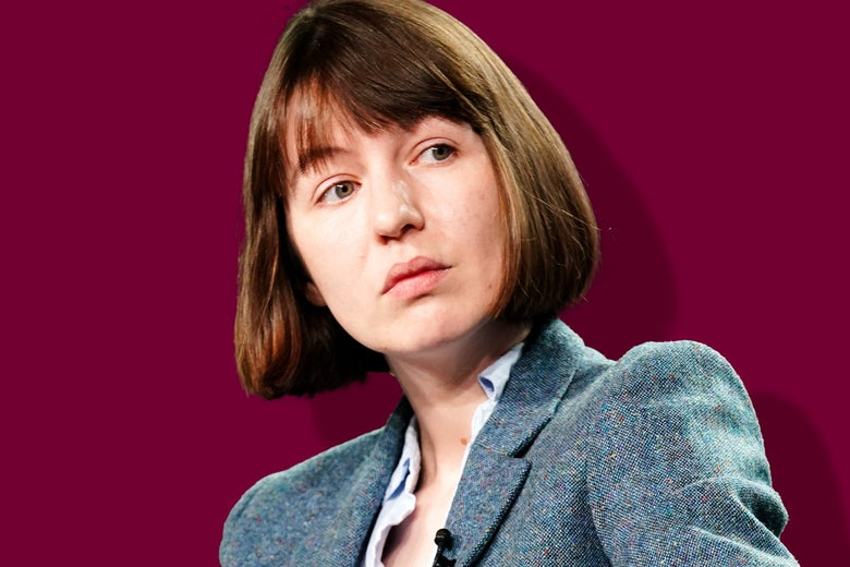 Sally Rooney in a bob haircut and a blazer, casting a sideward glance at someone off camera