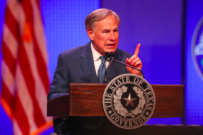 Texas Governor Greg Abbott speaks and points from behind a podium with the American flag over his shoulder.