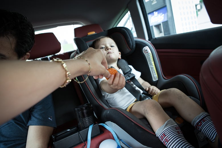 Rocco eating crackers in his car seat during a traffic jam.