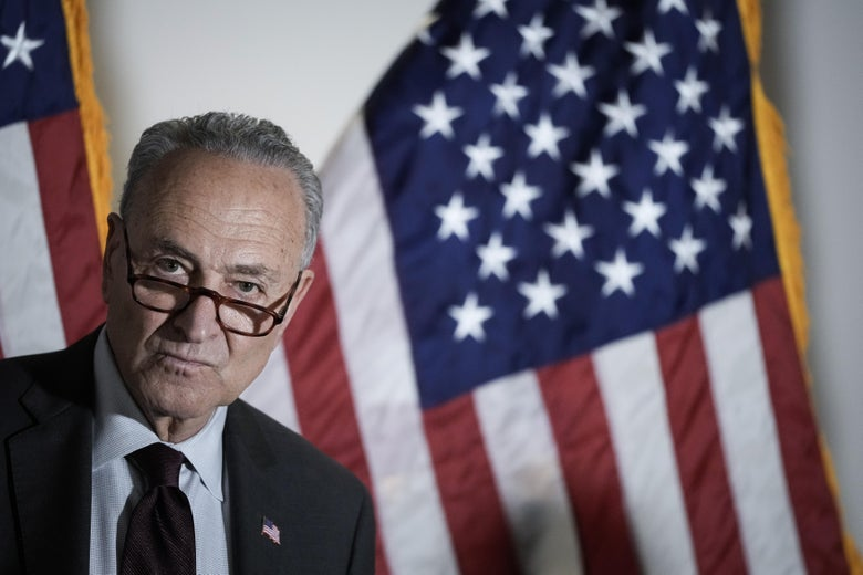 Chuck Schumer in front of an American flag.