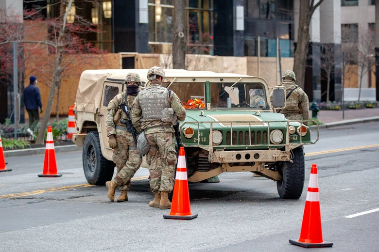 National Guard members in camo stand by a Humvee in the middle of a city street