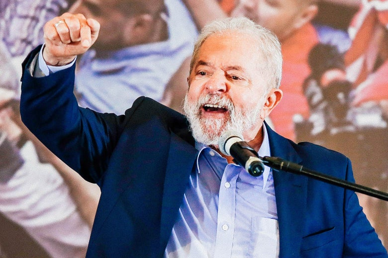 Lula raises his right fist as he speaks at a mic