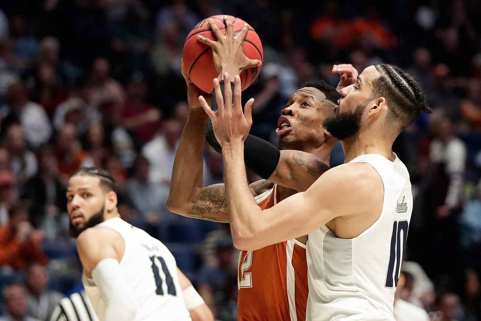 Texas guard Kerwin Roach II goes to the basket against Nevada forward Caleb Martin (10) in the second half of a first-round game of the NCAA college basketball tournament in Nashville, Tenn., Friday, March 16, 2018.
