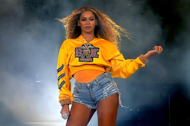 Beyonce Knowles, wearing a yellow sweatshirt and denim shorts, performs onstage during 2018 Coachella music festival.