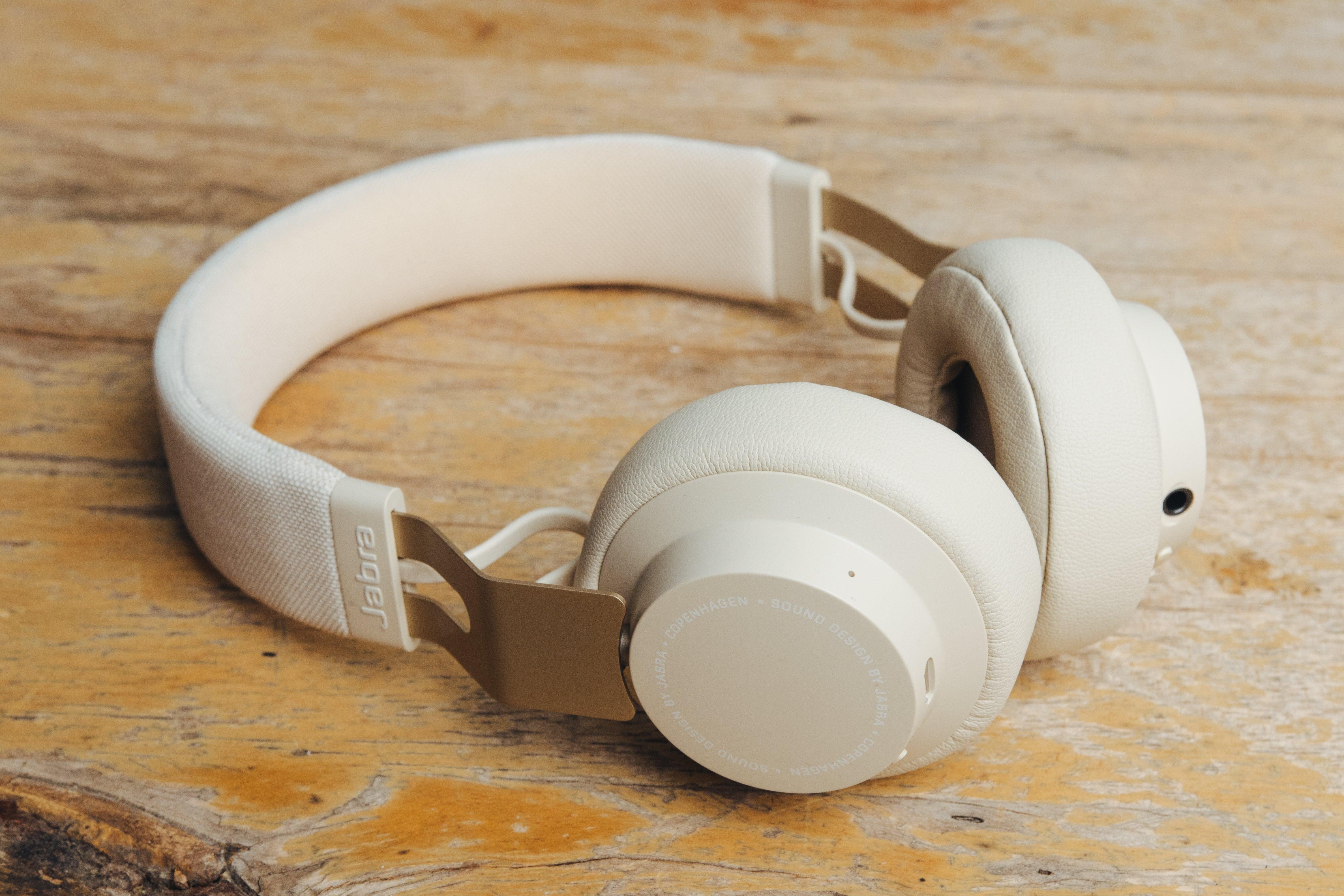 white Jabra headphones on wooden surface